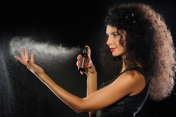 A portrait of a beautiful woman spraying perfume