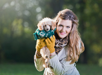Beautiful woman holding a small poodle