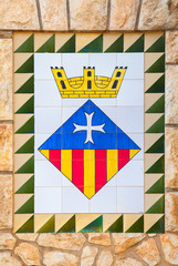 Calafell town Coat of arms on the old stone wall