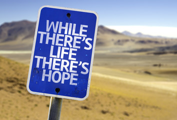 While There's Life There's Hope sign with a desert