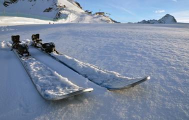 alpine skis on snow in sunset light