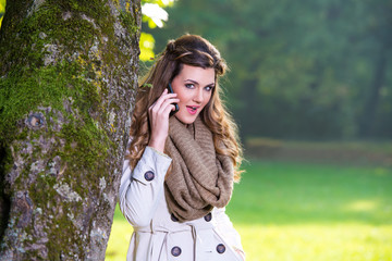 Beautiful young woman in the park talking on the cell phone