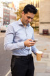 young man reading his text message and enjoying a coffee