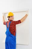 Smiling repairman gluing wallpaper poster