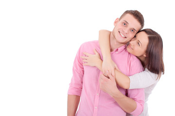 A young couple standing together and hugging.