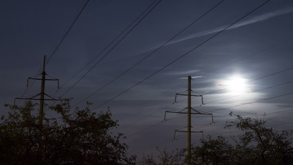 Moonrise over the power line. moon moves in the clouds