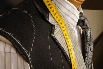 Tailor shop mannequin with measuring tape.