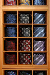 Fashionable collection of rolled-up ties in a retail setting.