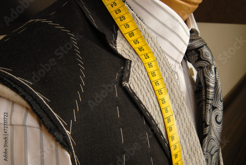 Tailor shop mannequin with measuring tape. - 72731722