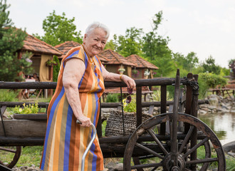 Smiling old woman with a cane in the garden