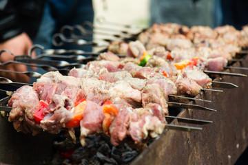 Marinated shashlik, meat grilling on metal skewer, close up