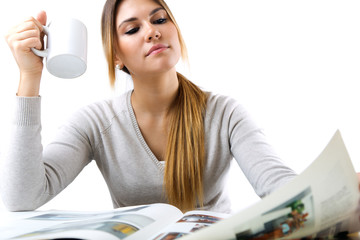 Young beautiful girl reading news and drinking coffee. Isolated
