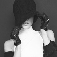 glamor model on black background in trendy gloves and hat autumn