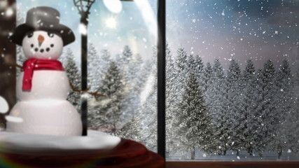 Snow globe on windowsill looking out to snowy forest