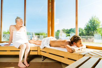 Seniorin und junge Frau schwitzen in Sauna
