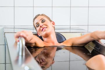 Junge Frau im Moorbad bei Alternativtherapie