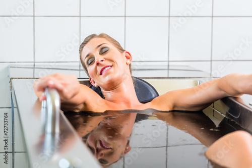 Leinwandbild Motiv Junge Frau im Moorbad bei Alternativtherapie