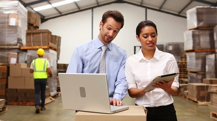 Warehouse managers looking at tablet pc and laptop