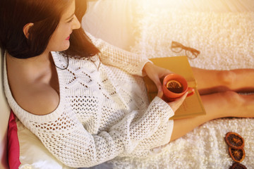 Pretty young girl relaxes at home with tea and a book