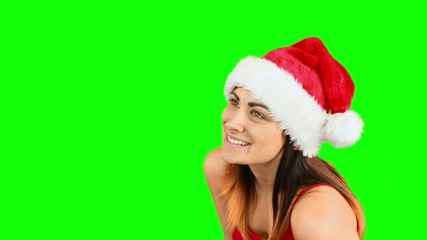 Pretty girl in santa hat blowing over hands