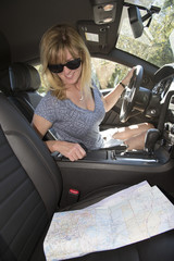 Female driver in sun glasses using map to plan route