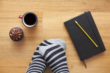 Feet with coffee cup, cupcake and diary with pencil