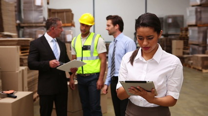 Warehouse managers talking while woman uses tablet pc