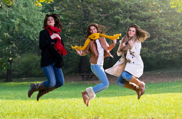 Three young women jumping joyfully in the park