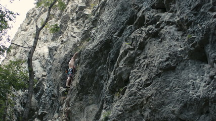 Man does difficult move while rock climbing in Turzii Gorge