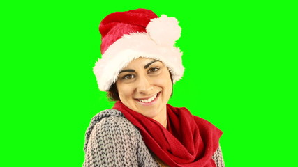 Pretty brunette in santa hat sending an air kiss to camera