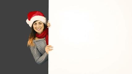 Beauty brunette in santa hat pointing white poster
