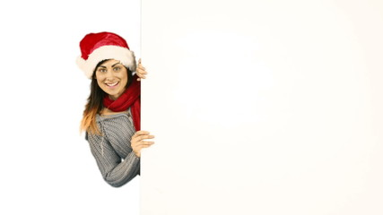 Beauty brunette in santa hat pointing white poster