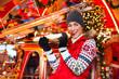 Frau isst beim Weihnachtsmarkt Bratwurst im Brötchen