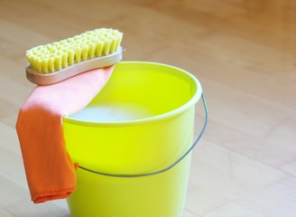Gelber Putzeimer und Bürste