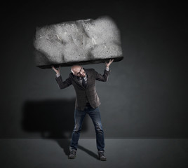 man with glasses holding a block of stone