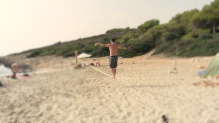 Man walks and falls off slackline on empty beach