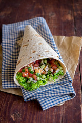 Tortilla wrap with fresh tomatoes, cucumbers, onion