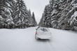 snow covered car on the winter road in forest