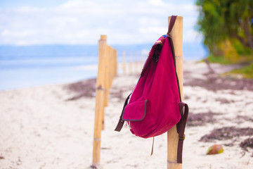 Red backpack at fence on exotic tropical beach