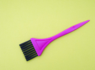 Tint, hair color dye application brush. Pink on bright green fab