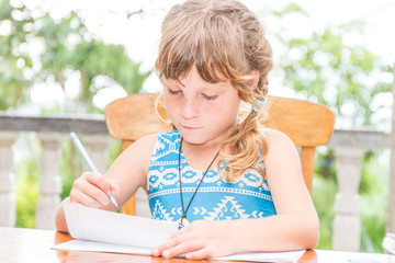 young child girl writing in notebook, outdoors portrait, educati