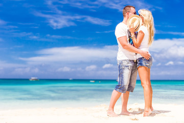 young loving couple relaxing on sand tropical beach on blue sky