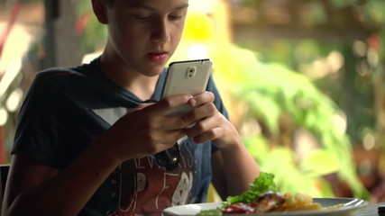 Young teenager taking photo of meal with cellphone in restaurant