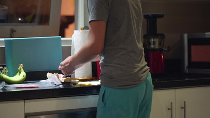 Young teenager preparing sandwich in kitchen at night