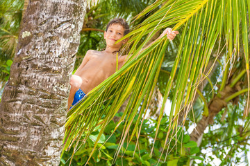 outdoor portrait of young happy child boy in tropical background