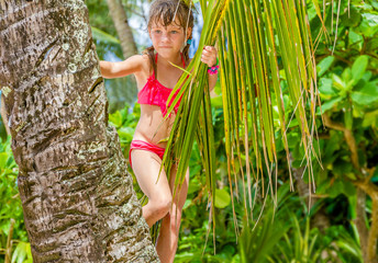 outdoor portrait of young happy child girl in tropical backgroun