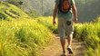 Man on trip, walking and hiking with backpack through terraces i