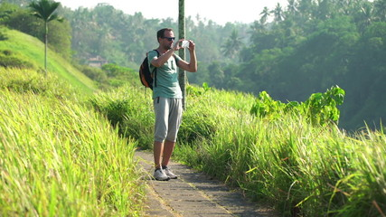 Handsome man talking photo with cellphone during trip in Bali