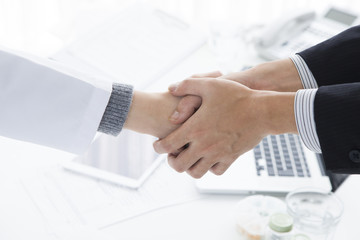 Doctor and salesman shaking hands