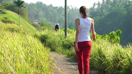 Woman on trip, walking and hiking through terraces in Bali